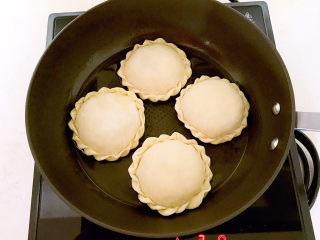 鸡蛋韭菜盒子,油烧到5分热的时候加入鸡蛋韭菜盒子生坯,全程小火煎制