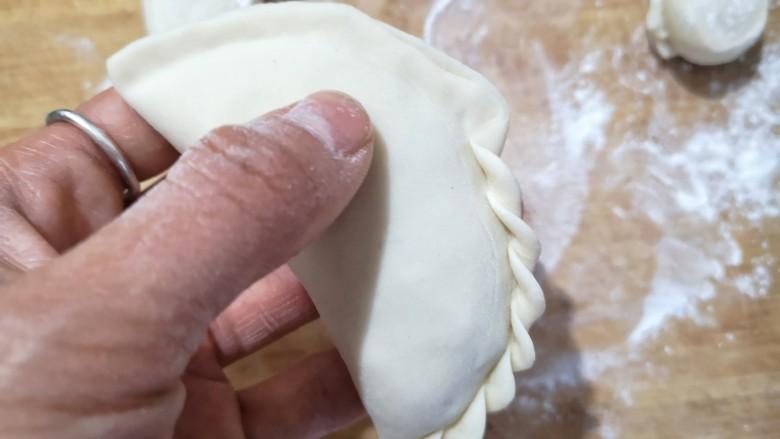 鸡蛋韭菜盒子,对折将边缘捏紧,捏出花边。