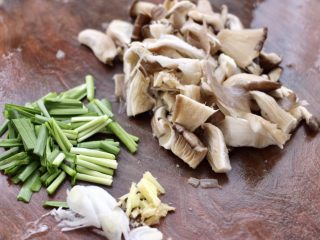 蘑菇海虾汤,蘑菇去根洗净后用刀切成块,韭菜切段,葱姜切碎备用。