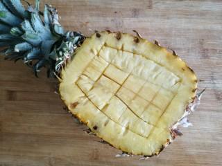 菠萝虾仁炒饭,菠萝洗净,从1/3处切开。将剩下2/3果肉打花刀切小块。