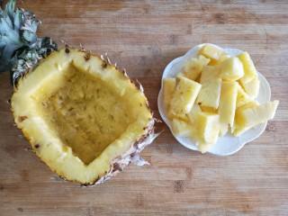 菠萝虾仁炒饭,用勺子将小块的菠萝肉挖出,留菠萝碗备用。