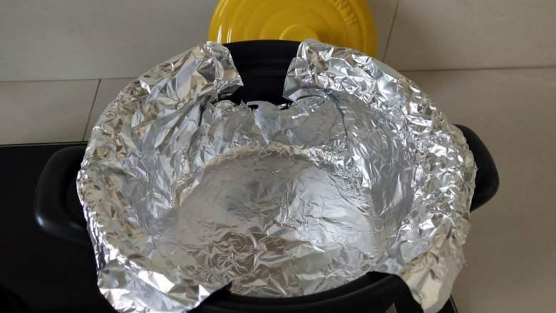 砂锅版烤鸡翅,取一张锡纸放入砂锅内,一圈紧挨锅壁,按服帖。