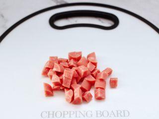 青口火腿青菜粥,火腿肠去掉外皮后,用刀切成小丁。