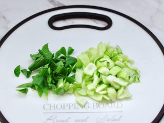 青口火腿青菜粥,青菜摘洗干净后,用刀切碎,注意根茎和叶分开区别。