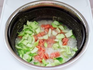 青口火腿青菜粥,烹饪至40分钟的时候,打开锅盖,锅中米粥已浓稠软烂了,这个时候先加入火腿丁和青菜的茎,盖上锅盖继续煮5分钟。