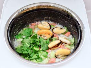 青口火腿青菜粥,再打开锅盖加入焯过水的青口和青菜叶。