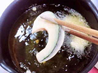 炸南瓜条,逐一将南瓜条制作好放入油锅中。