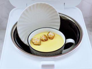 鲍鱼鹅蛋羹,蒸汽饭煲工作到12分钟时,打开锅盖,加入焯熟的鲍鱼,盖上锅盖再蒸3分钟焖2分钟即可。