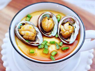 鲍鱼鹅蛋羹,取出蒸好的蛋羹,把鲍鱼肉放入鲍鱼壳中,淋上蒸鱼豉油和芝麻油,撒上提前切好的葱碎,就可以美美滴享用了。
