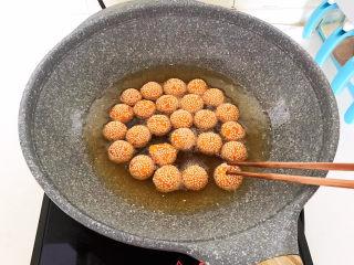 南瓜芝麻球,用筷子把每个南瓜芝麻球压一压,给南瓜芝麻球排排气