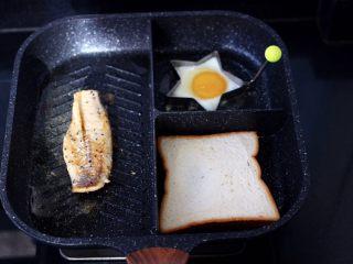 开放式鳕鱼鸡蛋三明治,把鳕鱼煎至两面金黄色,鸡蛋煎熟后,把吐司片放到煎锅里,两面加热即可。