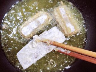 炸酥帶魚,鍋中倒入油,加熱至7成熱,逐一的放入帶魚。
