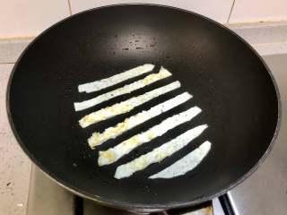 蛋包饭也可以萌萌哒,糖果的造型超吸睛!,锅里再刷一层油,把蛋清层出切成条,如图每条间隔一样的宽度的放入锅中。