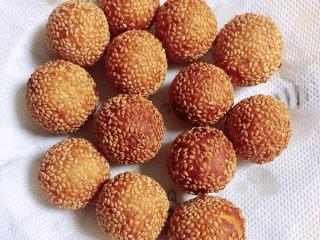 南瓜芝麻球,将炸好的南瓜芝麻球放入盘中,用吸油纸吸去多余的油。