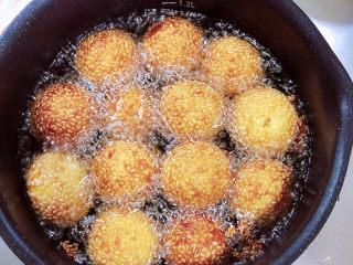 南瓜芝麻球,逐一放入南瓜球,南瓜球加热后慢慢漂起,炸至焦黄即可捞出控油。