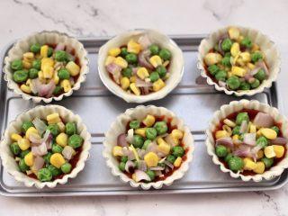虾仁时蔬迷你小披萨~饺子皮版,均匀的在每个饺子皮上码上焯过水的青豆和玉米粒,洋葱碎。