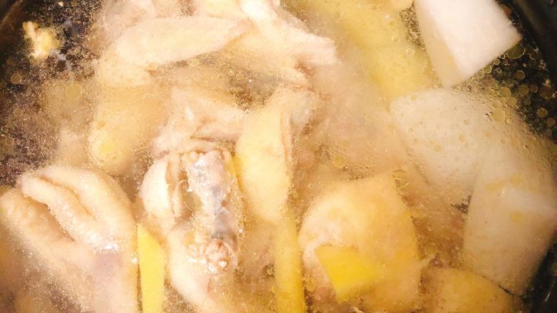 冬日暖身鸡汤,焯好水的鸡放入电饭锅中,锅中加入适量水同时放入土豆白萝卜一起煮