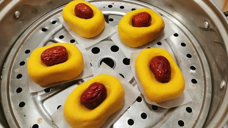南瓜糯米糕,蒸锅水烧开 将南瓜糕胚摆放到蒸屉上  每个南瓜糕胚底下铺一片烘焙纸 蒸15分钟 蒸熟