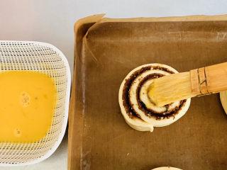 肉桂卷,发酵好的面团,明显变大,在面包坯上均匀的涂抹蛋液。