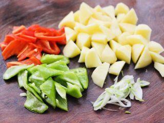 咖喱鸡肉土豆,把土豆去皮后,用刀切成滚刀块,青椒和红椒切片,葱姜切碎。