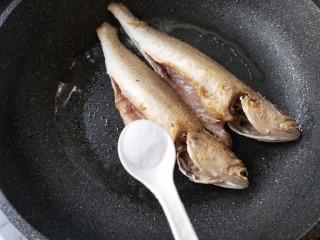酱焖黄花鱼,待鱼两面都煎至金黄后在鱼身上撒适量的盐。