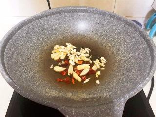 酱焖黄花鱼,炒锅烧热后加入大豆色拉油,油烧热后加入花椒粒和干红辣椒段,炒出香味,再加入葱姜,煸炒出香味