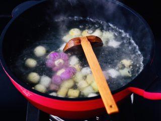 金桔圆子酒酿羹,大火煮沸后,用勺子搅拌均匀。