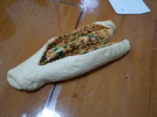 香葱肉松手撕面包,从一端轻轻卷起,收口朝下,从中间切开,注意另一头不能切断。