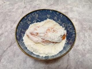 香酥炸鸡翅,先将腌好的鸡翅放入玉米淀粉里面,表面粘上一层玉米淀粉。