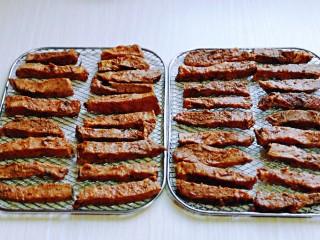 手撕牛肉干,腌制好的肉条摆放在网架上。