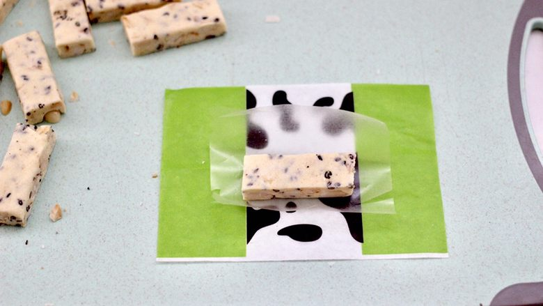 芝麻核桃糖,把切好的芝麻花生糖,先裹上一层糯米纸。