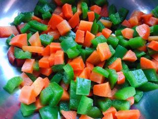 蔬菜虾仁粥,焯好水的青椒和胡萝卜粒立即放入冷水中过凉后沥干水分备用
