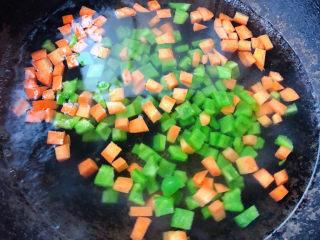 蔬菜虾仁粥,锅中烧开水放入切好的青椒粒和胡萝卜粒焯水时间不要过长刚刚变色漂浮起来即可