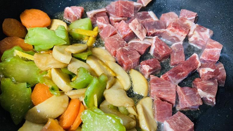 杏鲍菇炒牛肉,把杏鲍菇、胡萝卜、芥菜拨到锅边放入牛肉粒