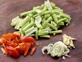 香辣八爪鱼,芹菜和红辣椒用刀切成条,葱姜切丝。