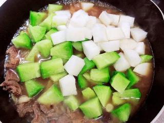 牛腩萝卜汤,牛腩煮开锅后,放入萝卜块,继续煮开锅。