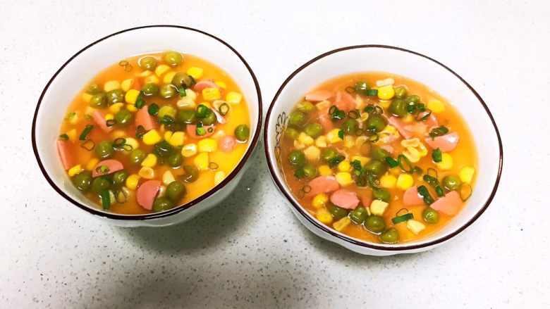 鸡蛋豆腐羹,把炒好的甜玉米青豆分别加入两个碗里,撒入香葱末,美味的鸡蛋豆腐羹就可以开吃了~