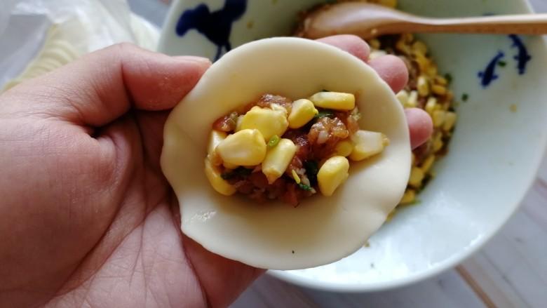 玉米猪肉饺,拿出一张饺皮,放上适量的馅儿