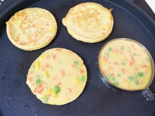 鸡蛋玉米饼,等到鸡蛋糊凝固以后,将煎蛋模具取开,饼翻面煎另一面,继续做下一个玉米鸡蛋饼。