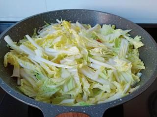 醋溜大白菜,加入白菜叶用铲子翻炒均匀。