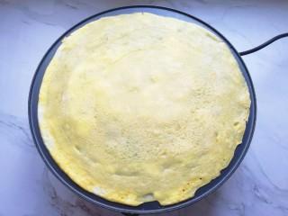 玉米渣煎饼,待蛋液凝固以后,将煎饼翻面。