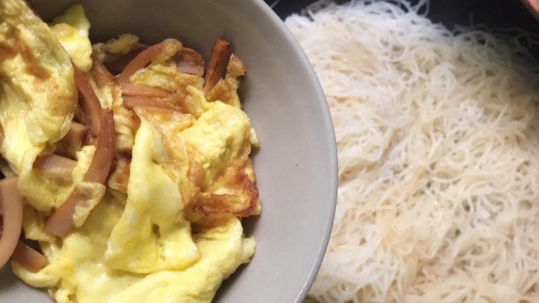 家常炒米粉,然后加入炒好的鸡蛋和火腿肠翻炒均匀