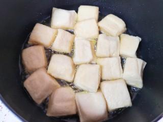 油菜豆腐,炸锅里倒多一点食用油烧热,放入小豆腐。