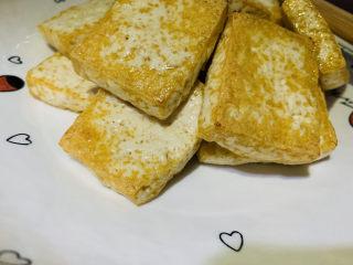 油菜豆腐,先把炸好的豆腐捞出放在盘里;