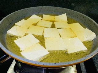 油菜豆腐,五成热时,把切好的豆腐放入油锅中炸;