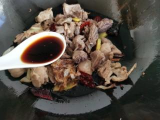 红焖羊肉土豆,加入料酒翻炒几下,再倒入老抽和生抽。