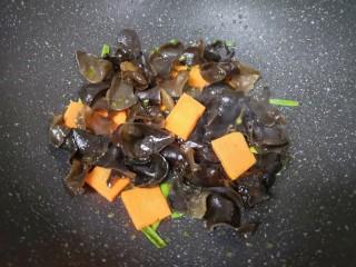 黄瓜木耳炒鸡蛋,下入黑木耳和胡萝卜翻炒均匀。