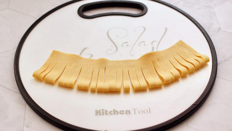 凉拌菊花豆皮,再用刀均匀的切成三毫米左右的细条,上面的地方不要切断。