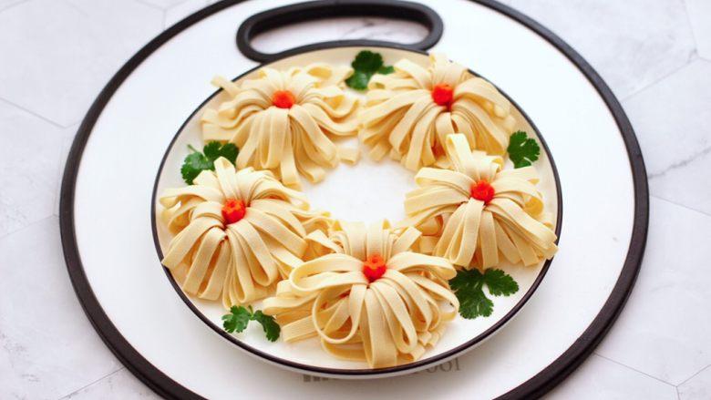 凉拌菊花豆皮,盘子边上随意点缀适量香菜叶。