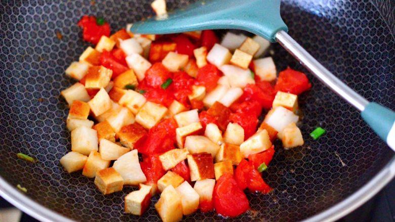 鸡蛋西红柿打卤面,锅中倒入剩下的15克花生油烧热,爆香葱花,先把番茄炒至变软,再加入豆腐干和杏鲍菇继续翻炒均匀。